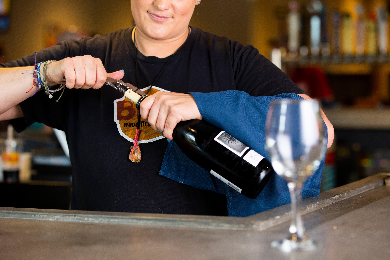 Girl opening bottle of wine behind wine glass