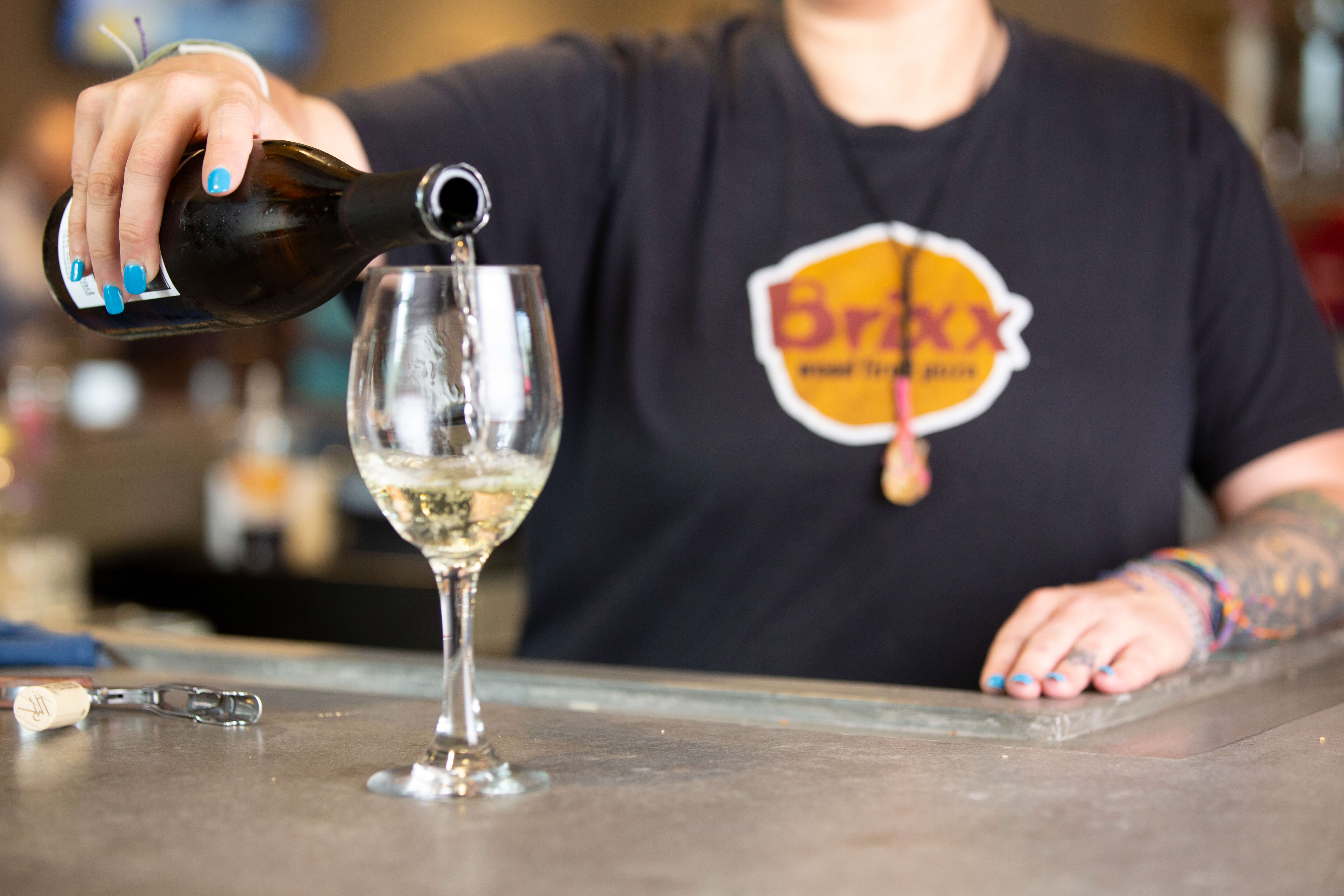 Girl pouring white wine into glass